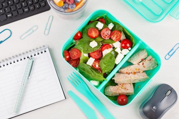 Boîte à lunch à emporter avec salade fraîche et thon sur le bureau avec des fournitures de bureau.