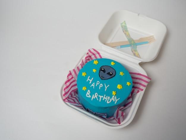 Boîte à lunch de gâteau coréen, gâteau avec l'inscription joyeux anniversaire et le visage d'un extraterrestre. place pour votre texte