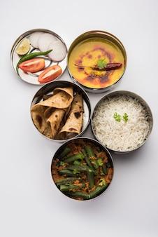 Boîte à lunch indienne végétarienne ou tiffin en acier inoxydable pour le bureau ou le lieu de travail, comprend dal fry, bhindi masala, riz avec chapati et salade