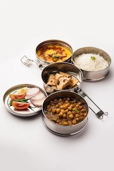 Boîte à lunch indienne végétarienne ou tiffin en acier inoxydable pour le bureau ou le lieu de travail, comprend dal fry, chole masala, riz avec chapati et salade