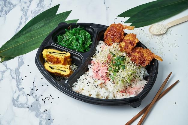 Boîte à lunch japonaise. riz blanc, frites de crevettes tempura, omelette traditionnelle japonaise et algues chuka sur blanc