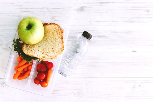 Boîte à lunch avec des légumes et une tranche de pain pour un déjeuner scolaire sain sur la table en bois