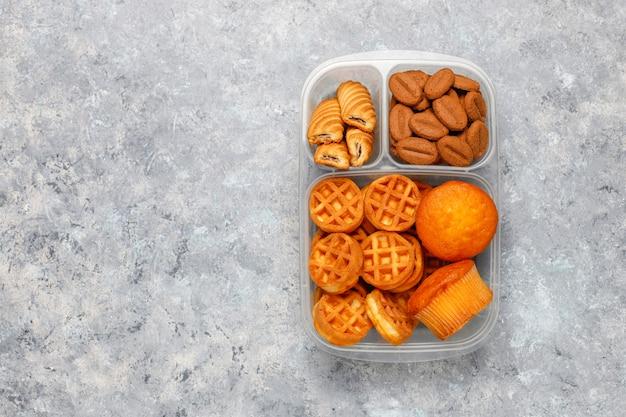 Boîte à lunch malsaine avec cookies, gaufres.muffins sur la surface en béton