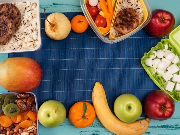Boîte à lunch avec de la nourriture appétissante et sur une table en bois clair