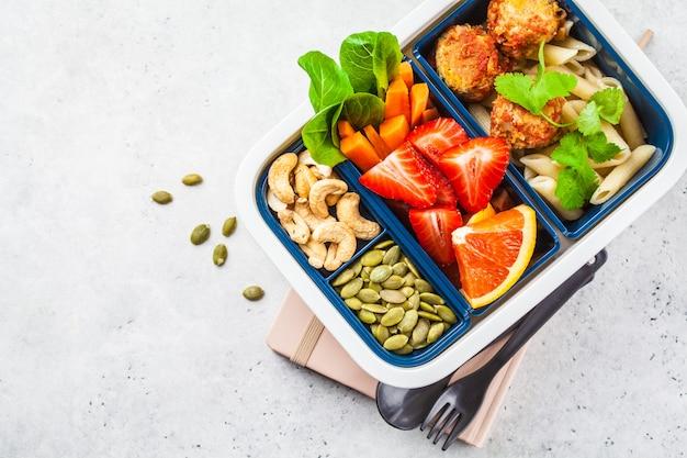 Boîte à lunch de nourriture saine. nourriture végétalienne: boulettes de viande de haricots, pâtes, légumes, baies, graines et noix dans un récipient