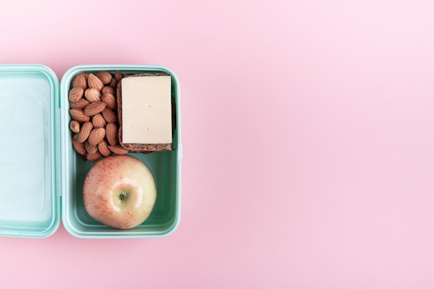 Boîte à lunch avec pomme, sandwich et amande rose