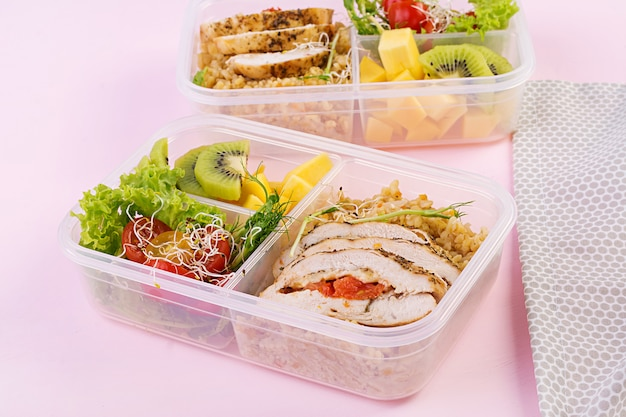 Boîte à lunch avec poulet, boulgour, micro-légumes, tomate et fruits