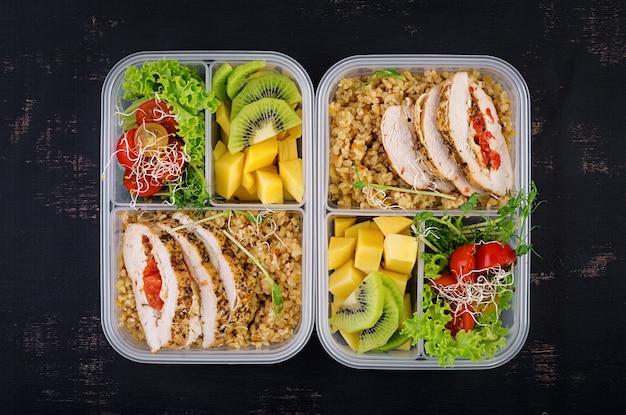 Boîte à lunch poulet, boulgour, micro-légumes, tomates et fruits.
