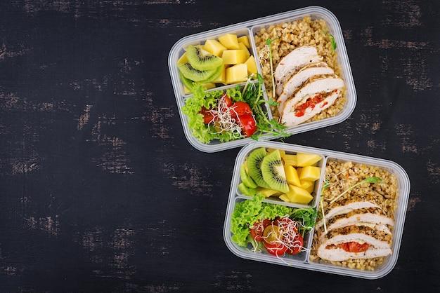 Boîte à lunch poulet, boulgour, microgreens, tomate et fruits. nourriture de remise en forme saine. à emporter. boîte à déjeuner. vue de dessus