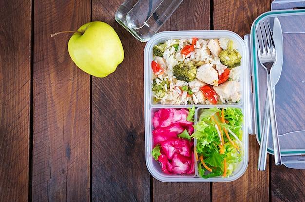 Boîte à lunch poulet, brocoli, pois verts, tomate avec riz et chou rouge. nourriture saine. à emporter. boîte à déjeuner. vue de dessus
