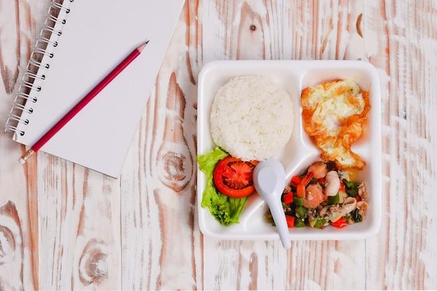 Boîte à lunch, riz frit au basilic et fruits de mer mélangés. , dans la boîte en mousse.