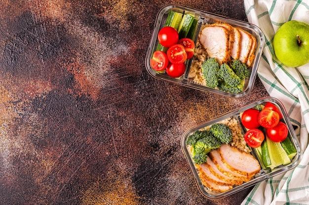 Boîte à lunch saine et équilibrée avec poulet, riz, légumes.