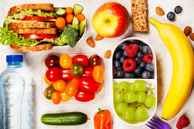 Boîte à lunch saine avec sandwich et légumes frais, bouteille de