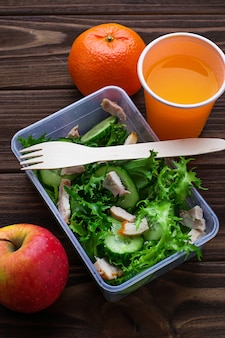 Boîte à lunch avec salade, pomme, mandarine et jus.