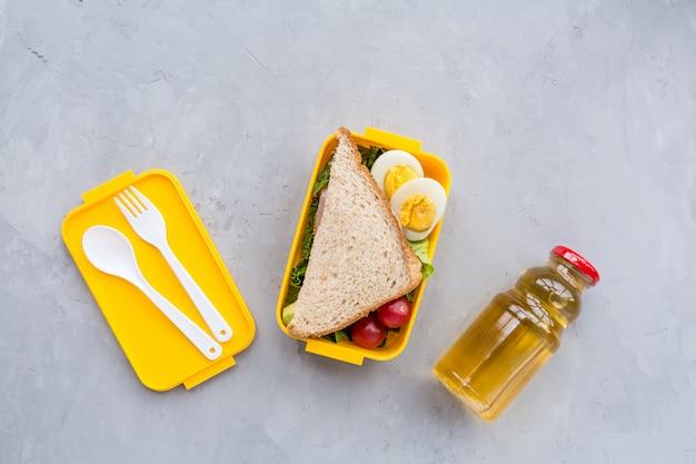 Boîte à lunch avec sandwich et différents produits sur fond gris