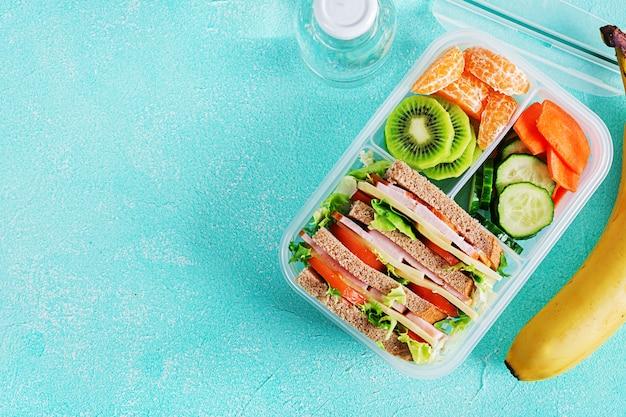Boîte à lunch avec sandwich, légumes, eau et fruits sur la table.