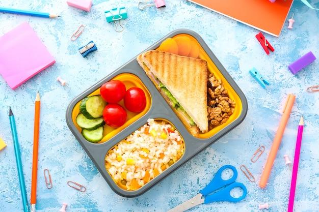 Boîte à lunch scolaire avec de la nourriture savoureuse et de la papeterie sur la couleur