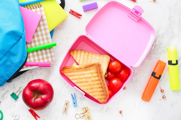 Boîte à lunch scolaire avec de la nourriture savoureuse et de la papeterie sur la table