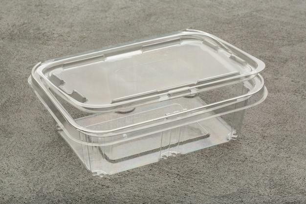 Boîte à lunch transparente en plastique jetable sur une table en béton gris.