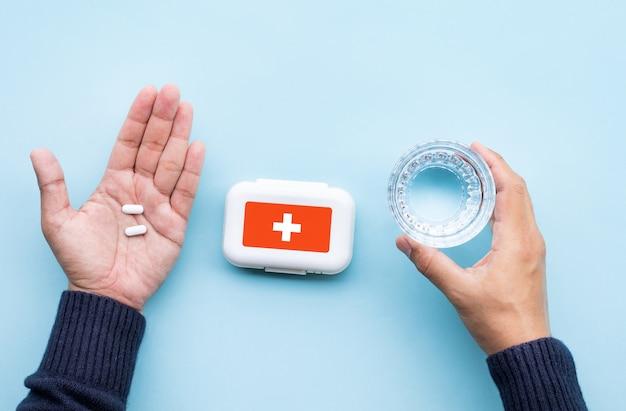 Boîte de médecine avec des pilules sur fond bleu