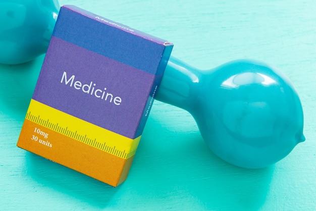 Boîte à médicaments et poids pour l'exercice physique symbolisant l'équilibre mental