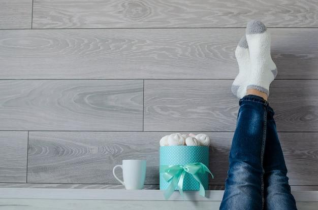 Boîte avec des meringues, une tasse blanche et des jambes de femmes vêtues d'un jean et chaussettes au mur