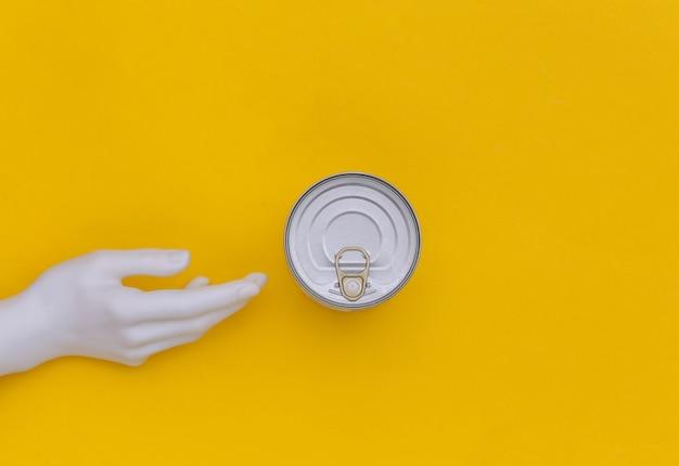 Boîte métallique de conserves et main de mannequin sur fond jaune. minimalisme. vue de dessus