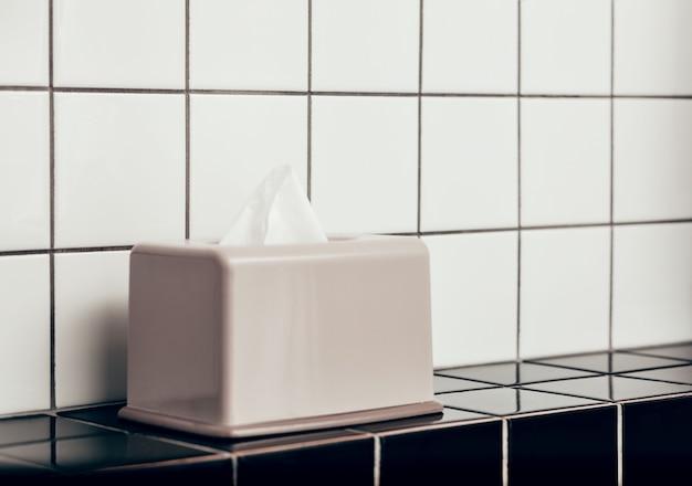 Boîte à mouchoirs et salle de bain sur carreaux de céramique