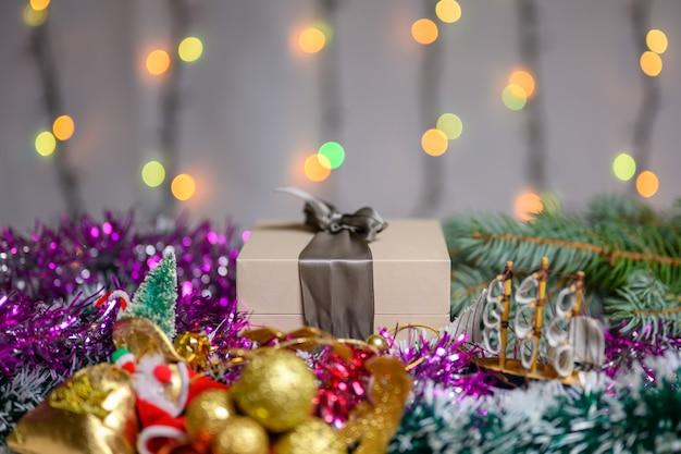 Boîte de noël avec un cadeau décoré de guirlandes et de jouets dans un ton froid et sur fond de guirlande scintillante.