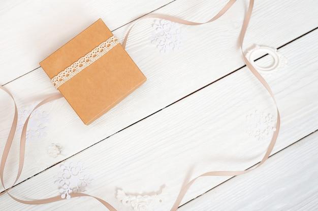 Boîte de noël avec du papier kraft et du ruban sur un fond en bois blanc