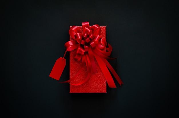 Boîte de noël rouge avec ruban arc rouge et étiquette de prix sur fond noir