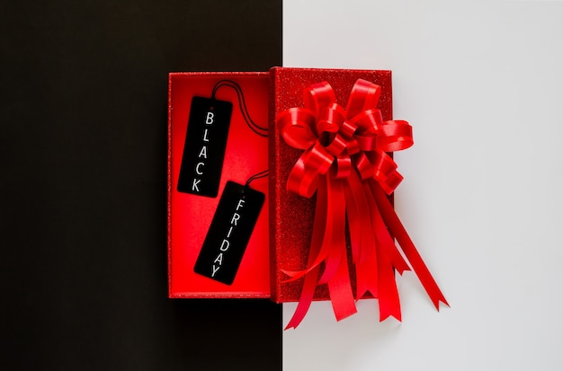 Boîte de noël rouge avec ruban arc rouge et étiquette de prix noir sur noir et blanc