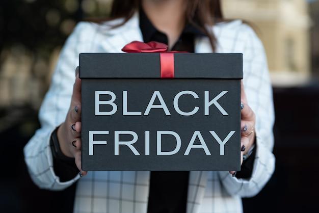 Boîte noire avec inscription black friday dans les mains des femmes. fille tenant une belle boîte-cadeau dans ses mains. fermer.