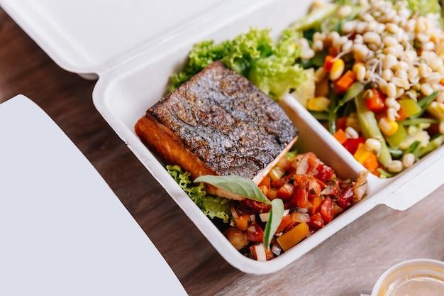 Boîte de nourriture propre: filet de saumon grillé avec salade de tomates et germes de soja.