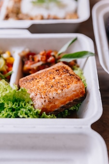 Boîte de nourriture propre: filet de saumon grillé avec salade de tomates et germes de soja