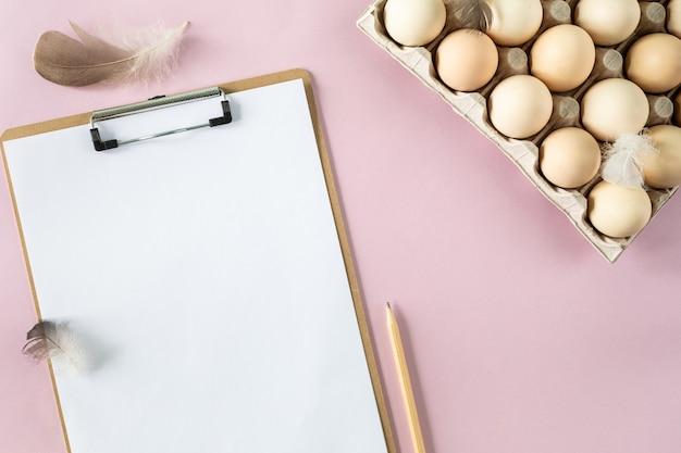 Une boîte d'oeufs de poule frais bio et un slipboard sur une table rose. production d'oeufs respectueuse de l'environnement. agriculture. ingrédients de cuisson. vue d'en-haut. copiez l'espace. horizontal.