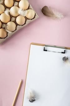 Une boîte d'oeufs de poule frais bio et un slipboard sur une table rose. production d'oeufs respectueuse de l'environnement. agriculture. ingrédients de cuisson. vue d'en-haut. copiez l'espace. verticale.