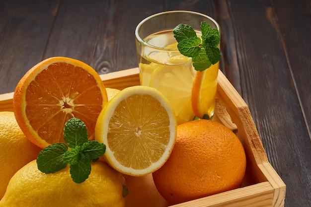 Boîte avec des oranges et des citrons juteux lumineux.