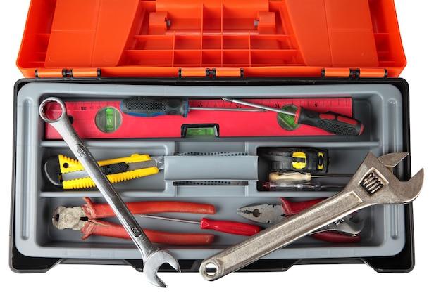 Boîte à outils en plastique noir orange avec ensemble d'outils anciens.
