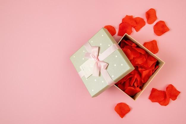Boîte ouverte remplie de feuilles de rose sur fond rose