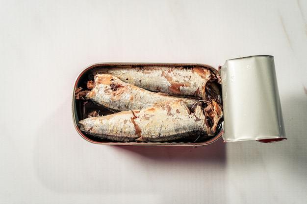 Boîte ouverte de sardines à l'huile isolée sur une surface en marbre blanc.