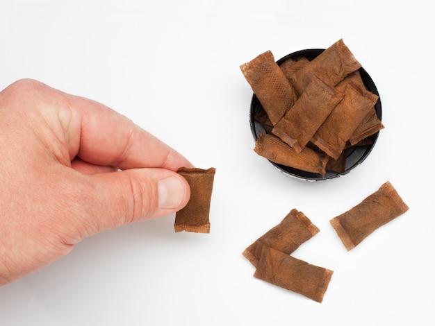 Boîte ouverte de tabac sans fumée avec la main de l'homme sur fond blanc vue de dessus