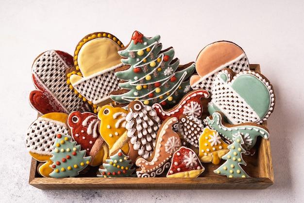 Une boîte de pain d'épice de noël sur fond gris. flocon de neige, sapin, mitaine, épicéa, étoile, traîneau, cônes, cône, étoile, forme de cloche.