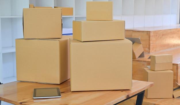 Boîte de papier brun et tablette sur le bureau dans le magasin de bureau, concept de transport de colis.