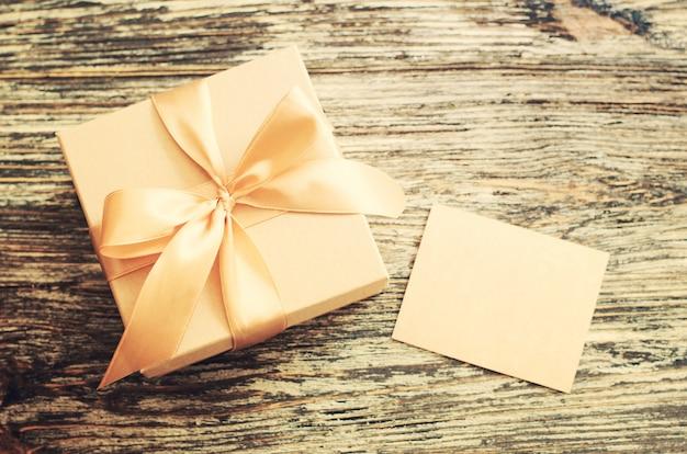 Boîte de papier cadeau artisanal avec ruban arc et étiquette vierge.