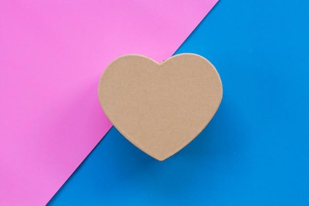 Boîte de papier en forme de coeur avec un fond de couleur.