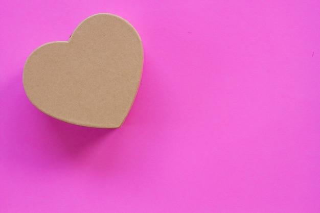 Boîte de papier en forme de coeur avec un fond rose.