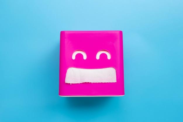 Boîte de papier de soie rose sur fond bleu.