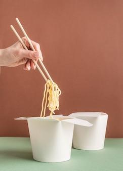 Boîte de papier wok ouverte pour la conception de maquettes. main de femme tenant des nouilles avec des baguettes