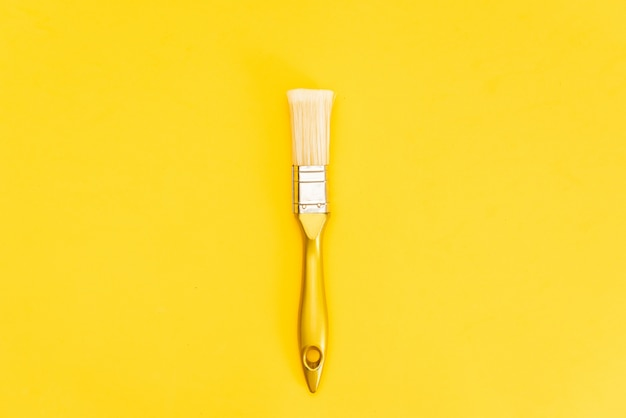 Boîte de peinture blanche avec vue de dessus de pinceau sur fond jaune.